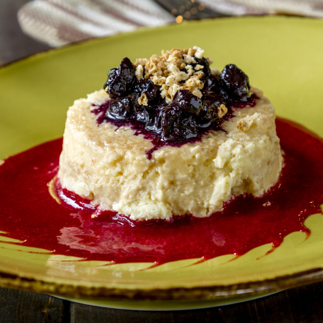 """Cheesecake topped with blueberries and raspberry sauce"" stock image"