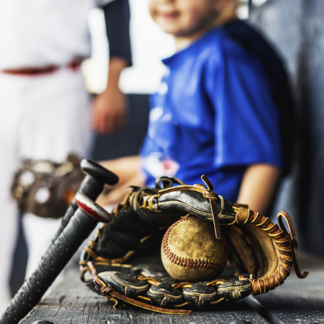 """Two ball players in uniform sit in the dugout with their glove and baseball..."" stock image"