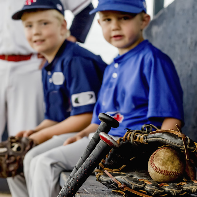 """A closeup focus on a game used baseball and glove with young boy players in..."" stock image"