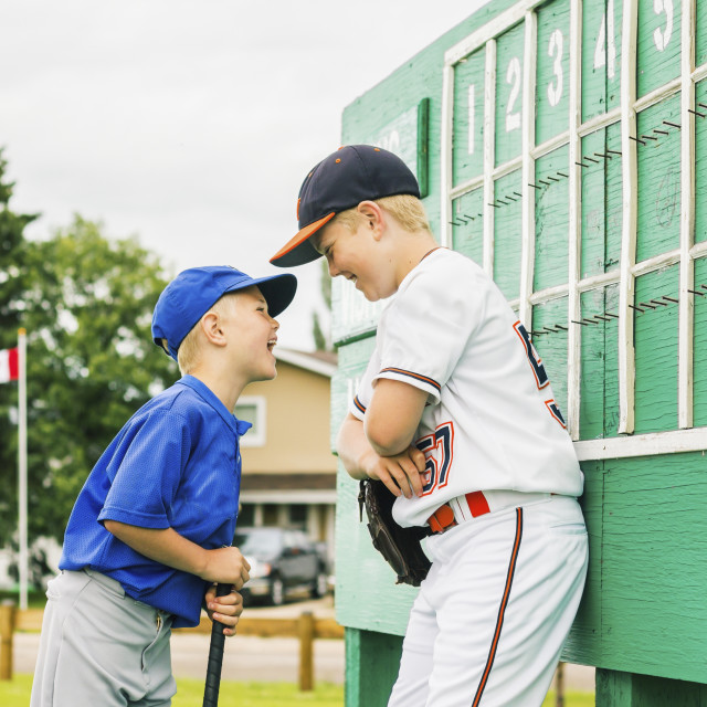 """Two boys in baseball uniforms playfully argue in front of the scoreboard..."" stock image"