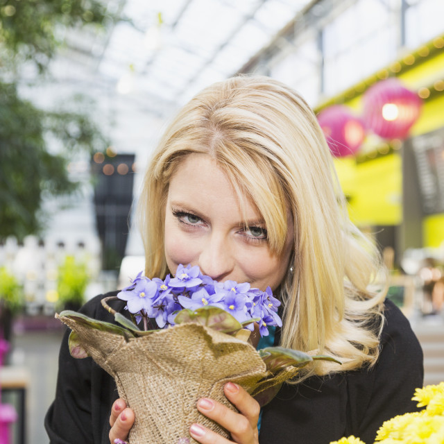 """Young woman looking at potted plants in a greenhouse store inside a mall; St...."" stock image"