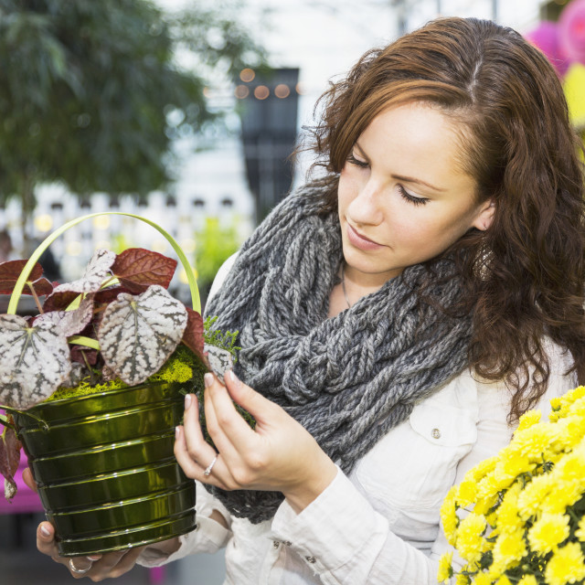 """Young woman looking at potted plants in greenhouse store inside mall; St...."" stock image"