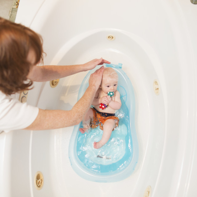 """""""Mother giving a child a bath in a bathtub, USA"""" stock image"""