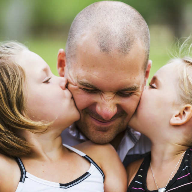 """""""A father holding his two daughters who are kissing him in a park; Edmonton,..."""" stock image"""
