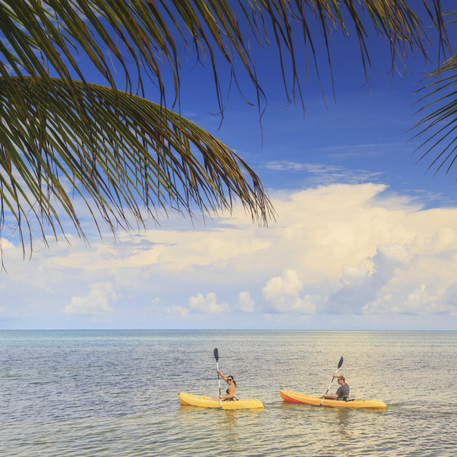 """""""A couple using kayaks at Saint Georges Caye Resort; Belize City, Belize"""" stock image"""