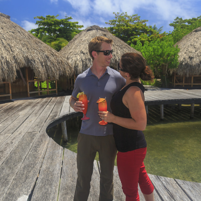 """""""Couple on a wooden boardwalk with refreshing drinks at Saint Georges Caye..."""" stock image"""