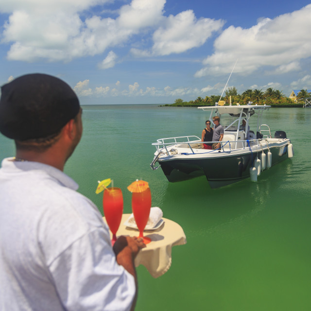 """""""A couple in a boat approaches a dock where a server is waiting with drinks,..."""" stock image"""