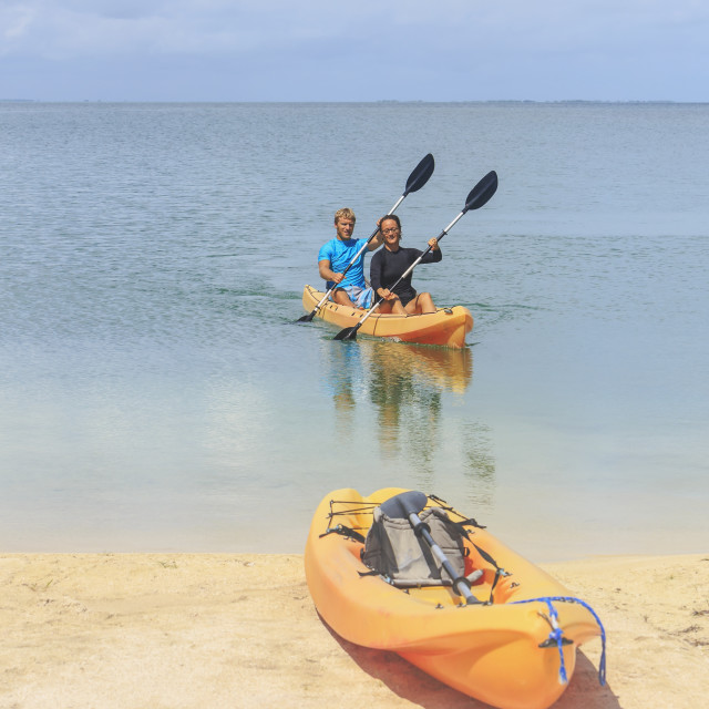 """""""A couple arriving at the beach in a kayak, Saint Georges Caye Resort; Belize..."""" stock image"""