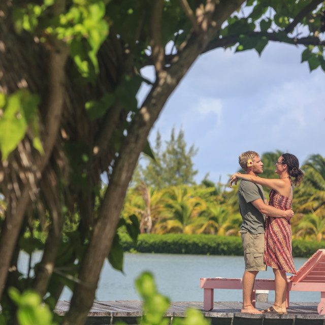 """""""Couple on a wooden dock in an embrace, Saint Georges Caye Resort; Belize..."""" stock image"""