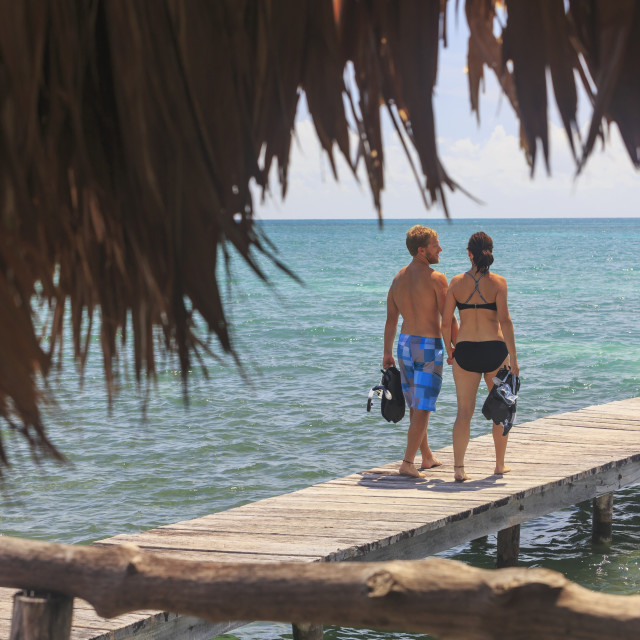 """""""A couple walks on a wooden dock with snorkelling gear, Saint Georges Caye..."""" stock image"""