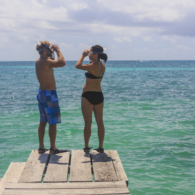 """""""A couple standing on a wooden dock with snorkelling gear, Saint Georges Caye..."""" stock image"""