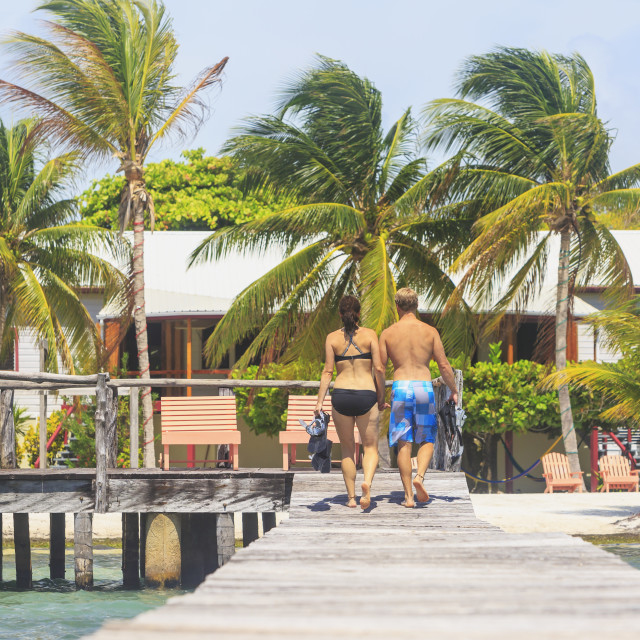 """""""A couple walking on a wooden dock, Saint Georges Caye Resort; Belize City,..."""" stock image"""