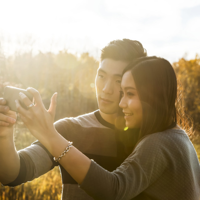 """""""A young Asian couple enjoying time together in a park in autumn and taking..."""" stock image"""