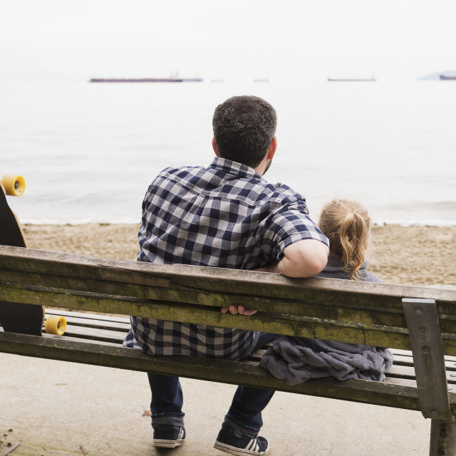 """""""A father and his little girl sit on a bench and watch the ships anchored in..."""" stock image"""