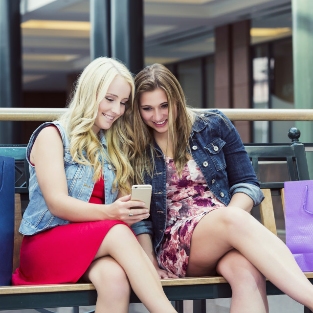 """""""Two beautiful young women out shopping and taking a break to check out social..."""" stock image"""