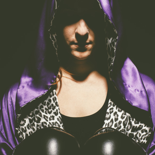 """""""A woman with a purple satin hooded cape over her head, an animal print shirt..."""" stock image"""
