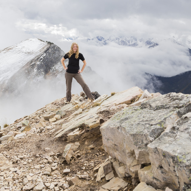 """""""A female hiker poses alone for an adventurous portrait at the peak of a..."""" stock image"""