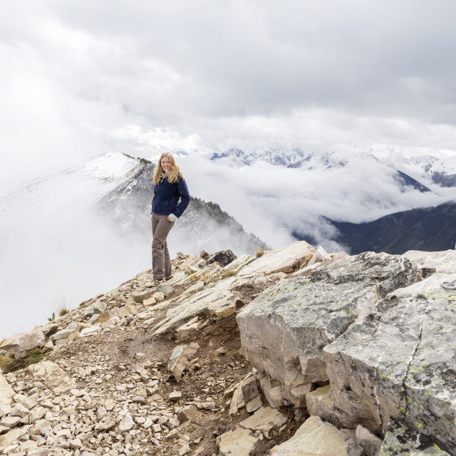 """""""A female hiker reaches the mountain summit and poses for a photo of the..."""" stock image"""