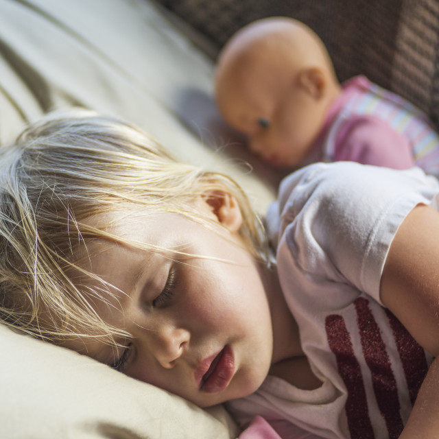 """""""A caucasian toddler with blond hair naps with her doll; Penn Yan, New York,..."""" stock image"""