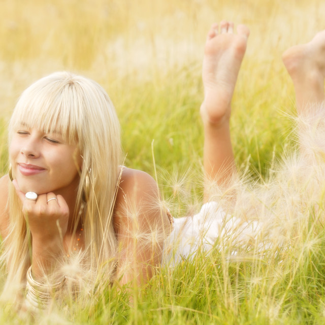 """Teenager Girl Lying In Grass Wishing"" stock image"