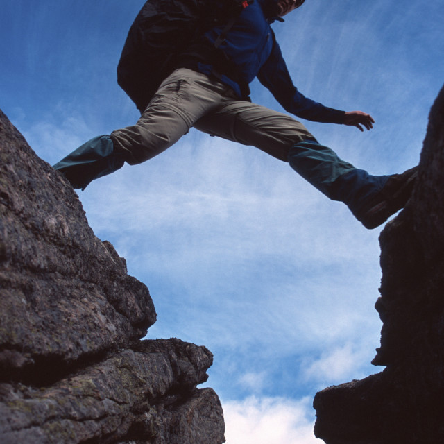 """Hiker Jumping Across A Gap"" stock image"