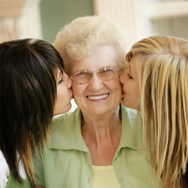"""Grand Daughters Kissing Grandmother"" stock image"