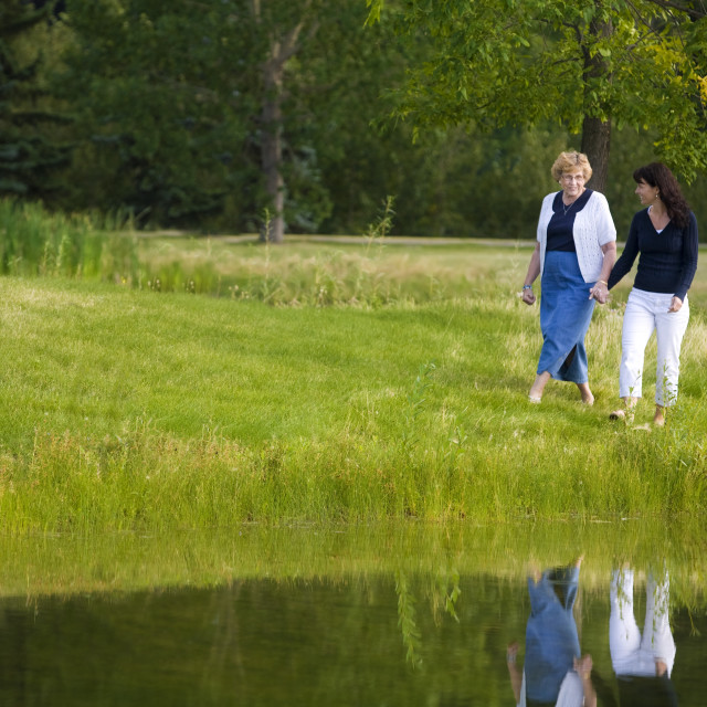 """Two Women Walking Beside A Lake"" stock image"