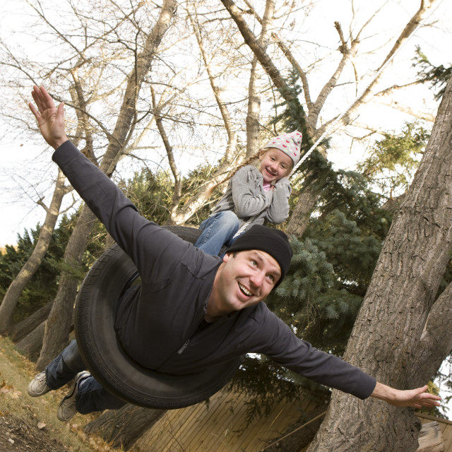 """""""Father And Daughter On Tire Swing"""" stock image"""