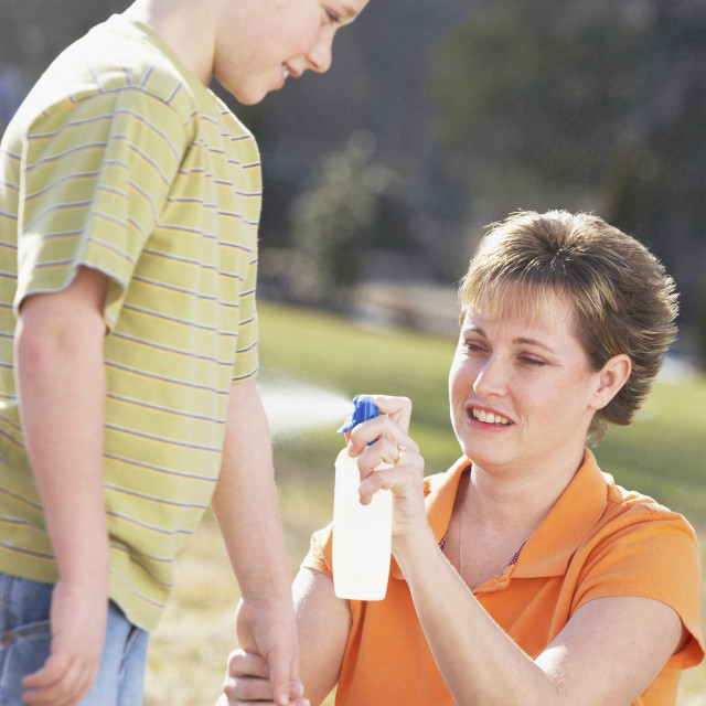 """""""A Mother Spraying Insect Repellent On Her Son"""" stock image"""