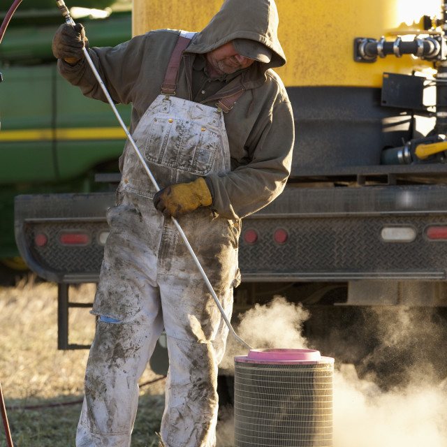 """A Person Cleans A Filter For Farm Equipment; Three Hills, Alberta, Canada"" stock image"