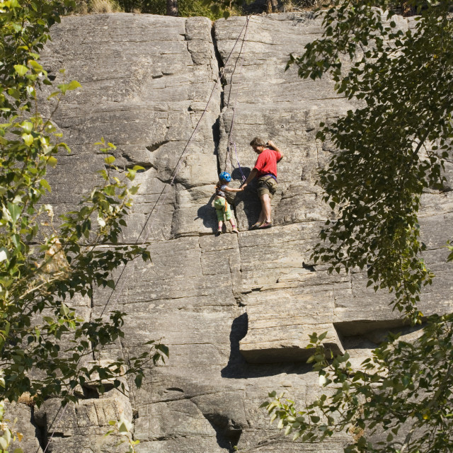 """""""Mid-Aged Man Helping Daughter Tie Climbing Rope At Base Of Cliff, Near..."""" stock image"""