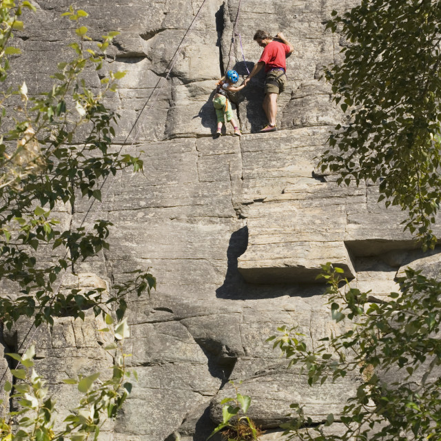 """""""Mid-Age Man Climbing With Daughter (Age 5) Up Granite Cliff At Stone Hills..."""" stock image"""