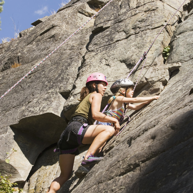 """""""Young Woman Climbing With Daughter (Age 7) Up Granite Cliff At Stone Hills..."""" stock image"""