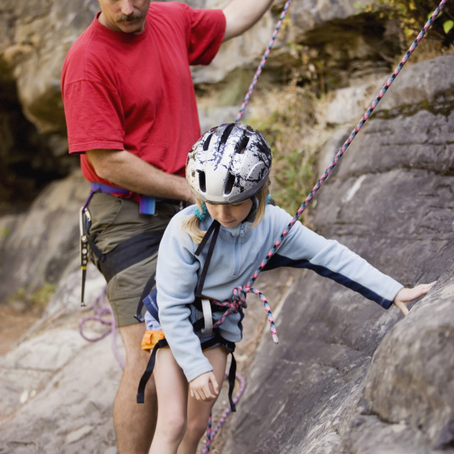 """""""Young Girl (Age 7) Preparing To Climb While Father Belays At Stone Hills Near..."""" stock image"""