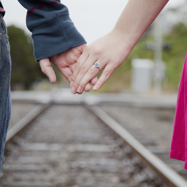 """""""An Engaged Couple Holding Hands Walking Down Railroad Tracks; Bellingham,..."""" stock image"""