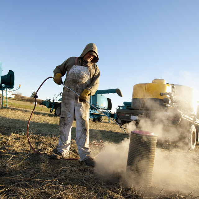 """A Man Cleaning Farm Equipment; Three Hills, Alberta, Canada"" stock image"