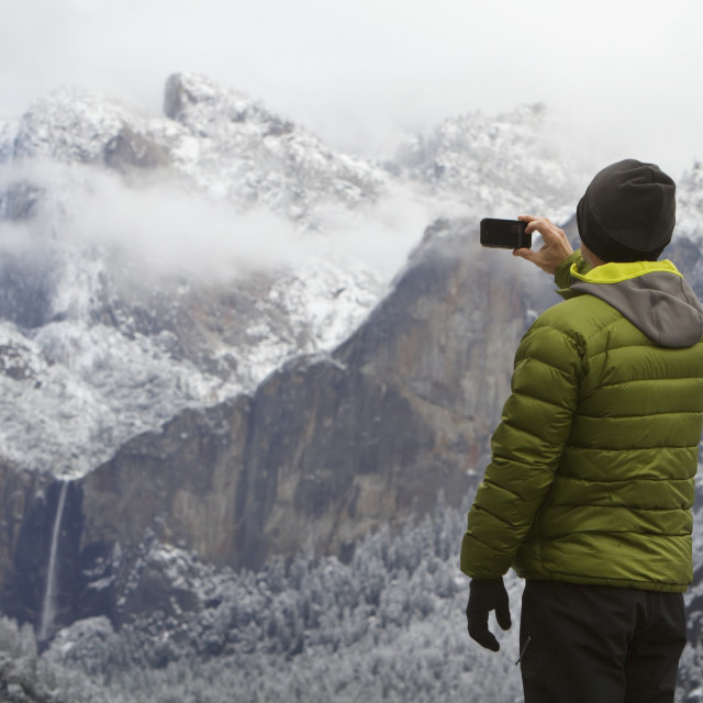 """Man wearing a green down jacket, as seen from the back, taking a picture of..."" stock image"