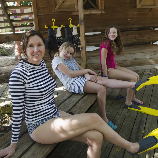 """A Mother And Two Daughters Sit On A Wooden Bench With Flippers On Their Feet;..."" stock image"