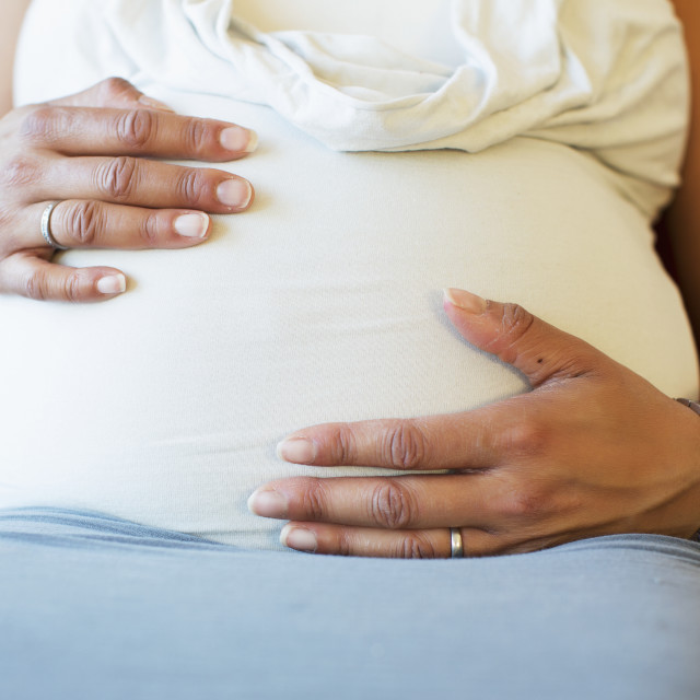"""""""A pregnant mother putting hands on her belly; Toronto, Ontario, Canada"""" stock image"""