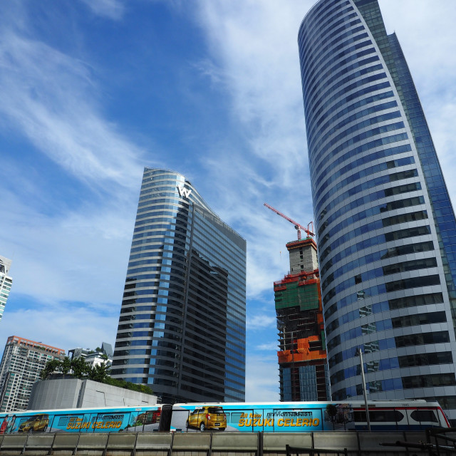 """A BTS Skytrain passes in front of modern office buildings"" stock image"