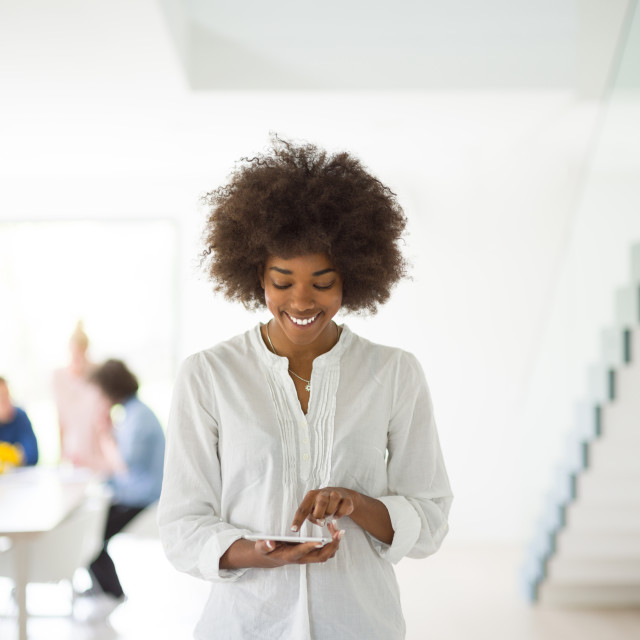 """""""Portrait of black casual businesswoman using tablet with coworkers standing..."""" stock image"""