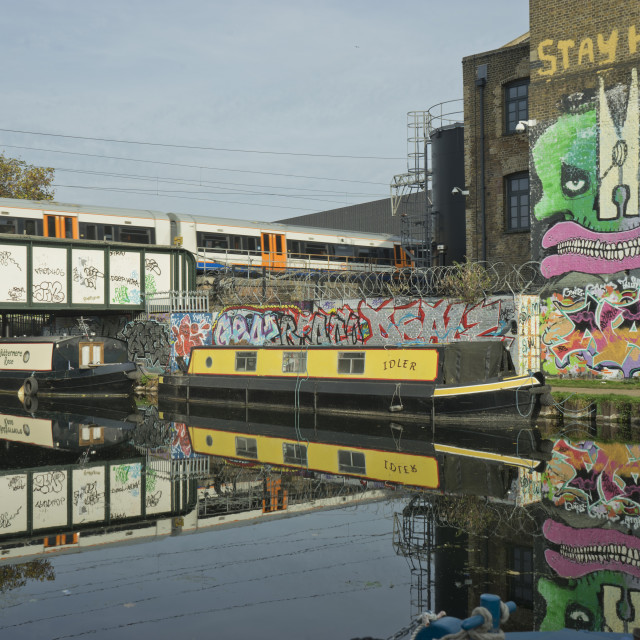"""""""Overground train drives past canal by artists studios and warehouses in..."""" stock image"""