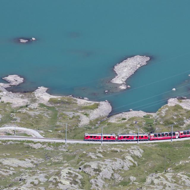 """The Bernina Express train passes on the shores of Lago Bianco, Bernina Pass,..."" stock image"