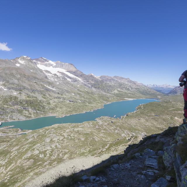 """Hiker admires the blue alpine lake from Pizzo Campaccio, Bernina Pass, Canton..."" stock image"
