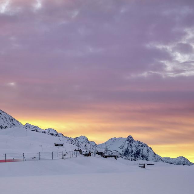 """""""Pink clouds and snow frame the Bernina Express train at dawn, Bernina Pass,..."""" stock image"""