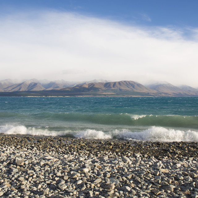 """View from rocky shoreline across the stormy waters of Lake Pukaki, near..."" stock image"