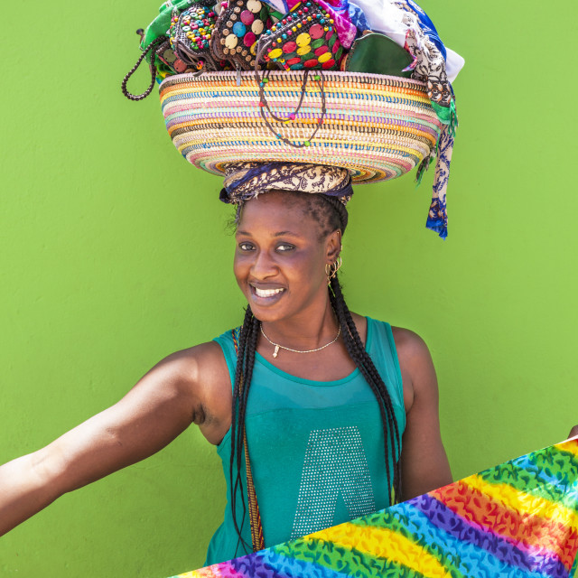 """Local woman with basket on her head selling souvenir scarves and jewellry,..."" stock image"