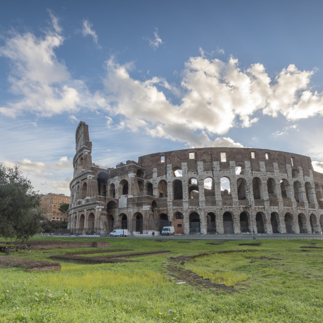 """Blue sky at sunrise frames the ancient Colosseum also known as Flavian..."" stock image"