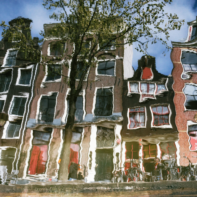 """The reflection of typical narrow houses with large windows in the canal, Amsterdam"" stock image"