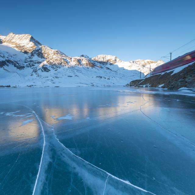 """The Bernina Express train runs beside the frozen Lago Bianco Bernina Pass..."" stock image"
